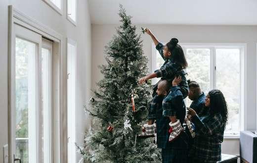 A girl putting a christmas star on a christmas tree