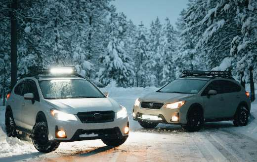 Two white suvs on snow covered road