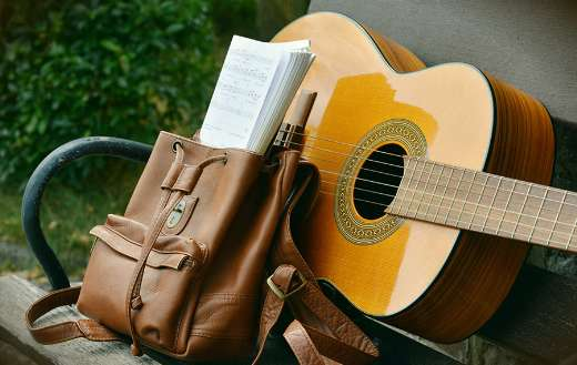 Brown acoustic guitar and brown leather backpack