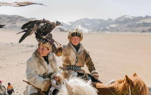 Positive Mongolian eagle hunters riding horses on mountainous terrain