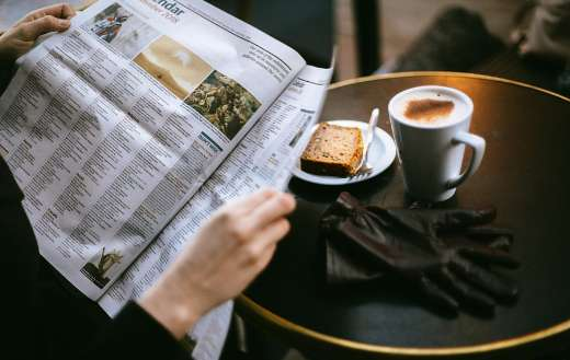Photo of person reading with coffee bread