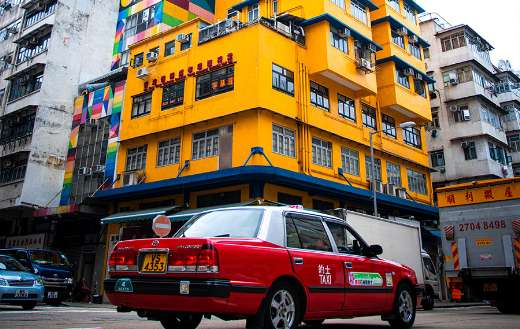 Red taxi passing classic yellow old building Hongkong