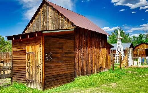 Brown wooden barn under blue sky