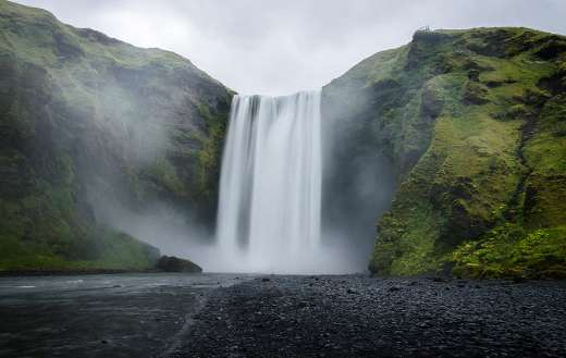 Water falls on the green covered mountain during daytime