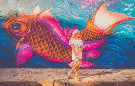 Woman standing near fish graphic wall